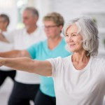 A multi-ethnic group of adult men and women are indoors in a fitness studio. They are wearing casual clothing while at a yoga class. A senior Caucasian woman is smiling while stretching out her arms.