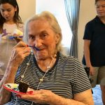 Resident Phyllis Norris enjoys a piece of birthday cake.