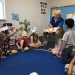 Students joyfully interact with David Baad as he reads.